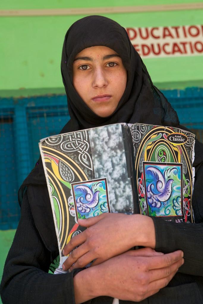 Girl in burka behind notebook