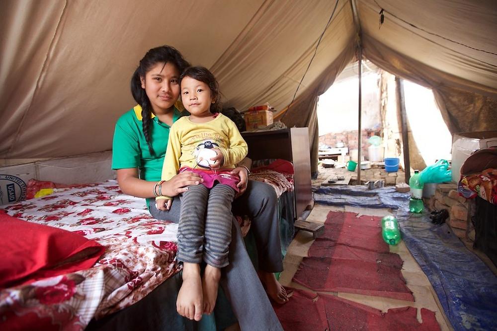 Two girls inside tent, one holding solar light
