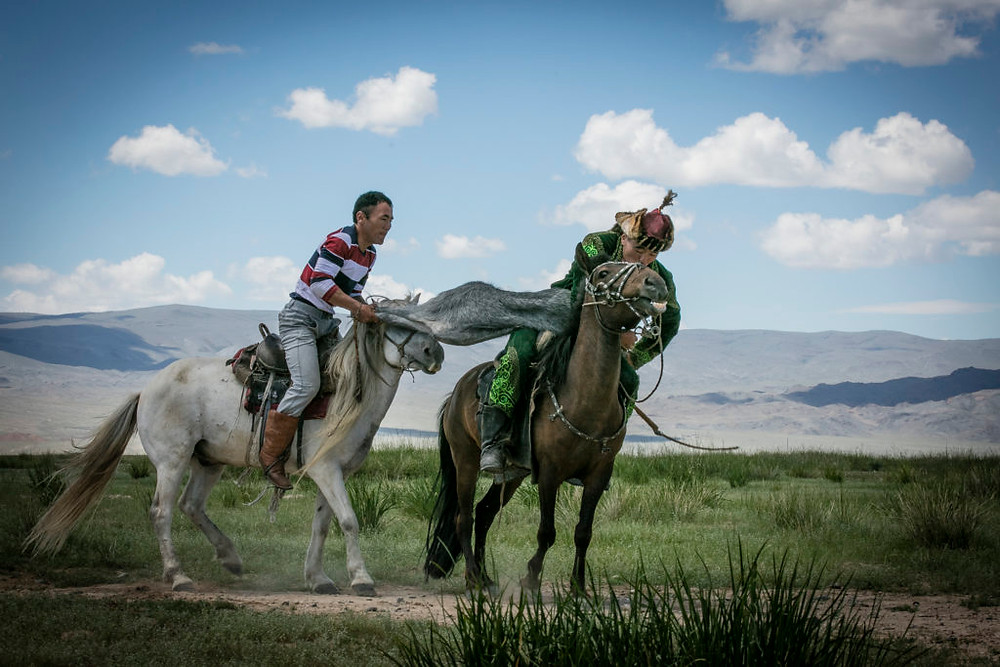 Two men struggle for the goat carcass on horses