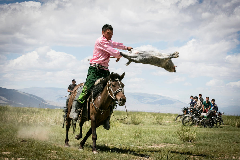 Man throws goat carcass as men on motorbikes watch