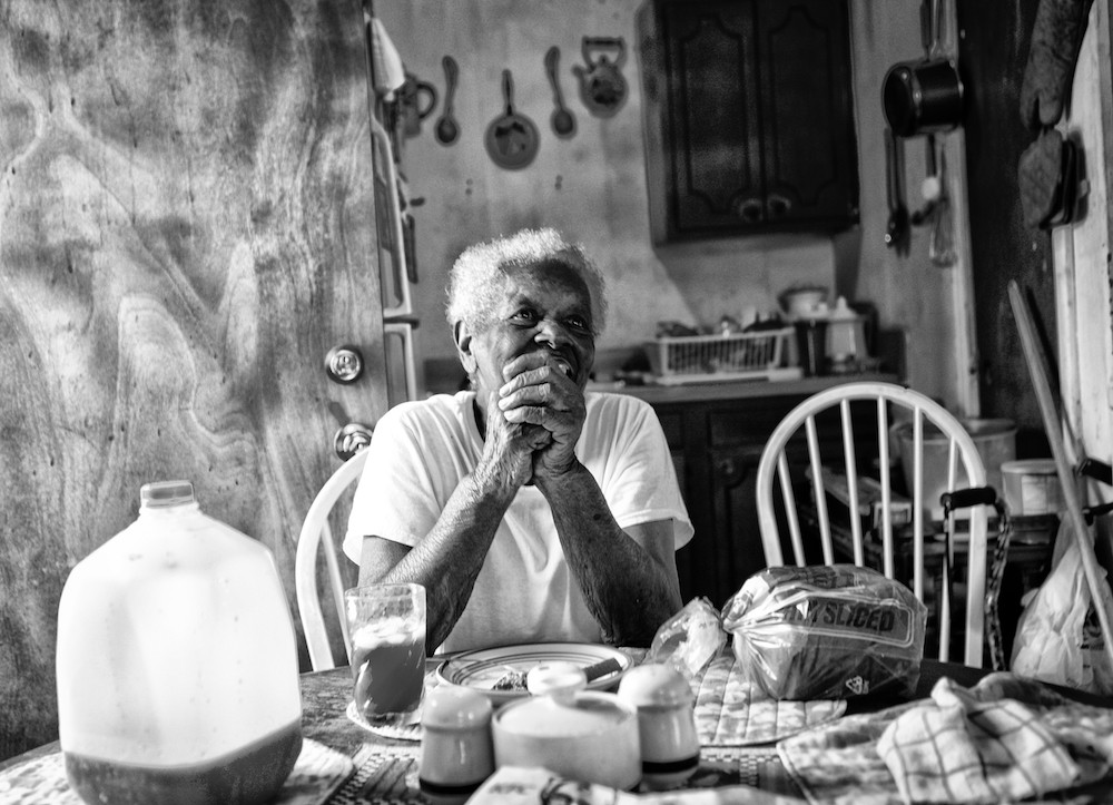 Elderly person sitting at table with loaf of bread