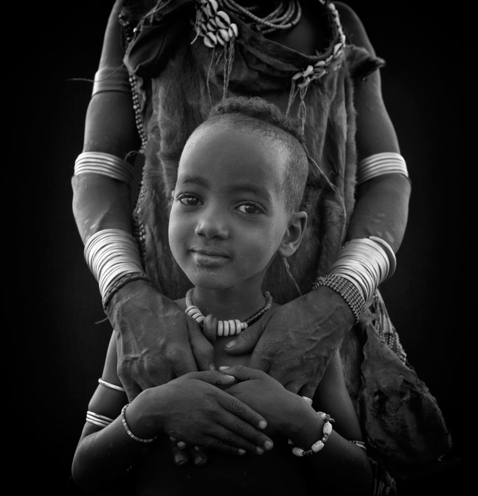 Omo River Valley child, held by woman behind him