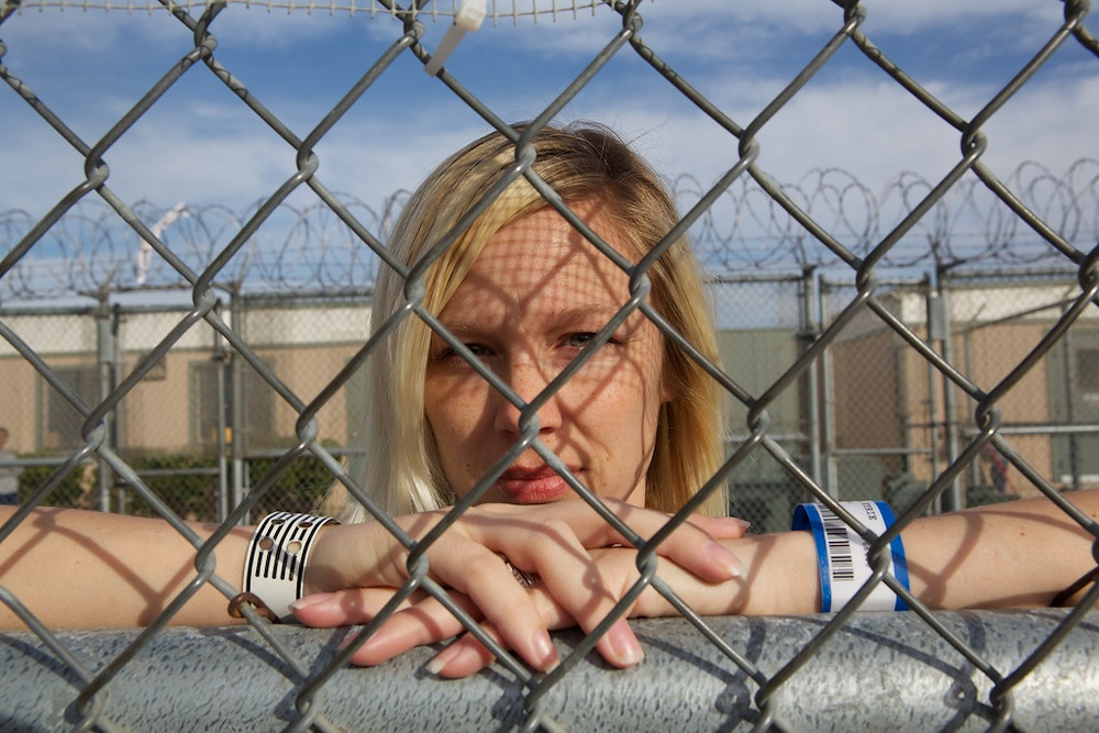 Woman looking through chain link fence