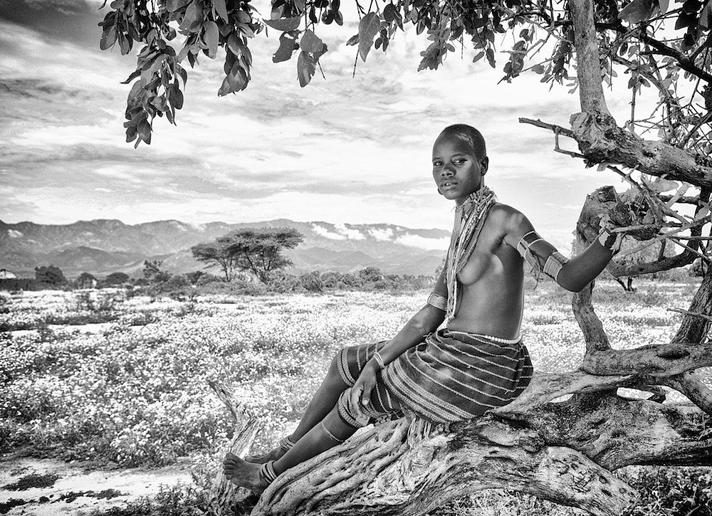 Omo River Valley beauty reclining on tree trunk