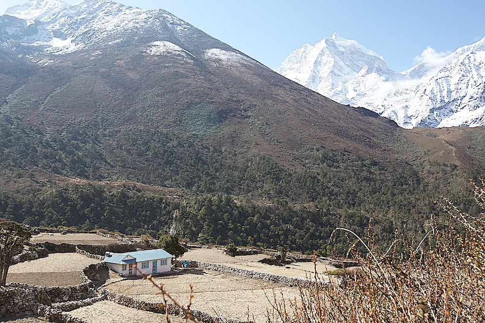 house in foreground Himalayas in background
