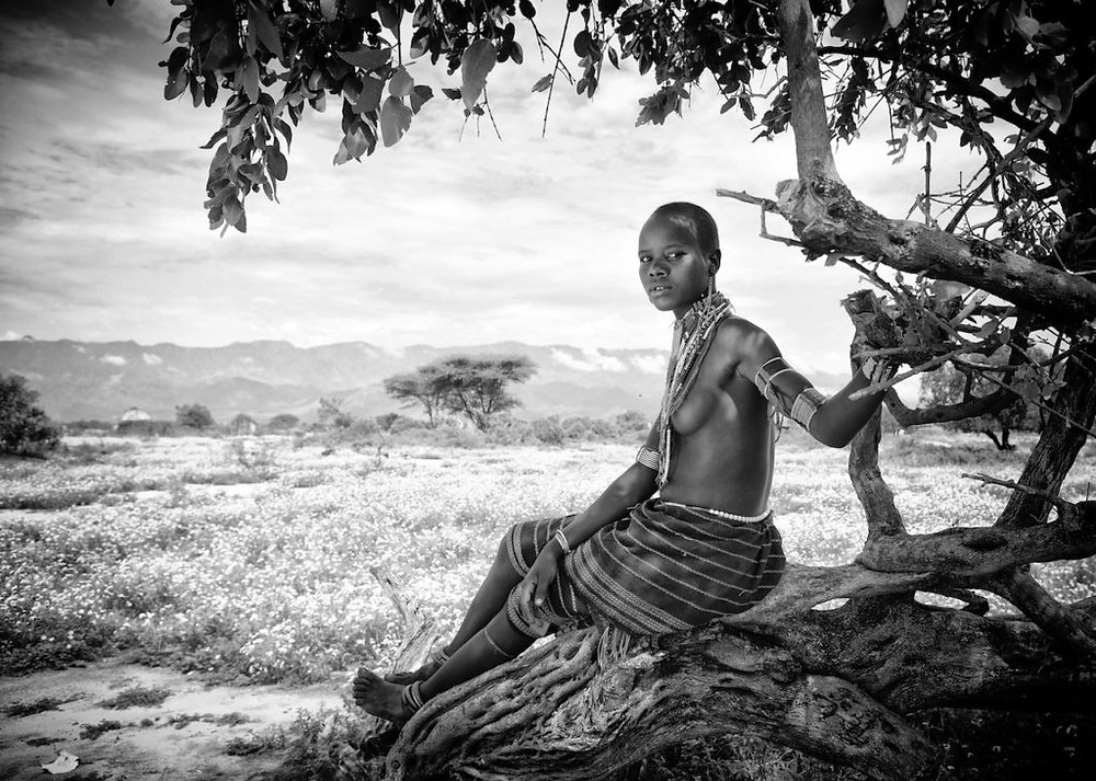 African tribeswoman sitting on tree
