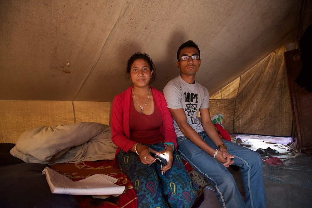 Man and woman sitting inside tent