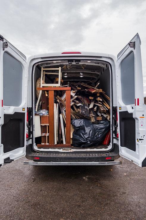 White work van full of debris and on its
