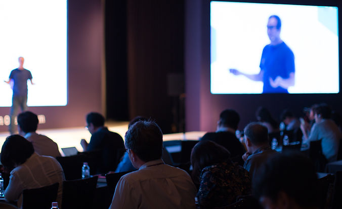 conference attendees facing away from camera in a darkened conference room, with speaker on stage