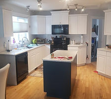 Updated kitchen cabinets from a wood stain to clean white upper and lower cabinets with a blue island.