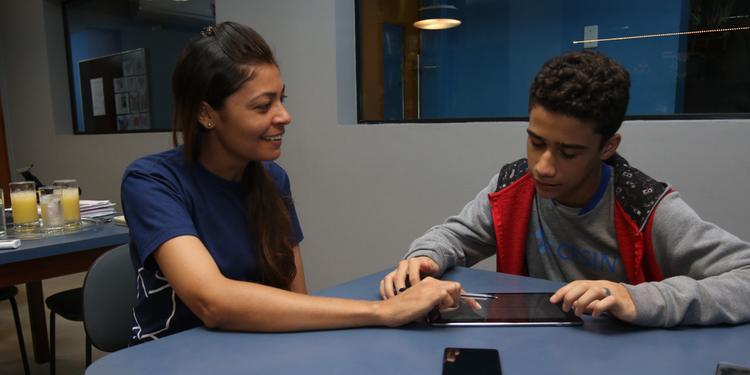 Professora auxilia aluno com iPad