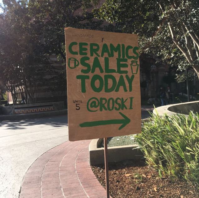 A sign directing students to the ceramics sale.