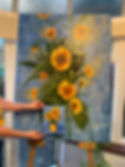 a photograph of a large oil painting of a sunflower and a small acrylic painting of  sunflower