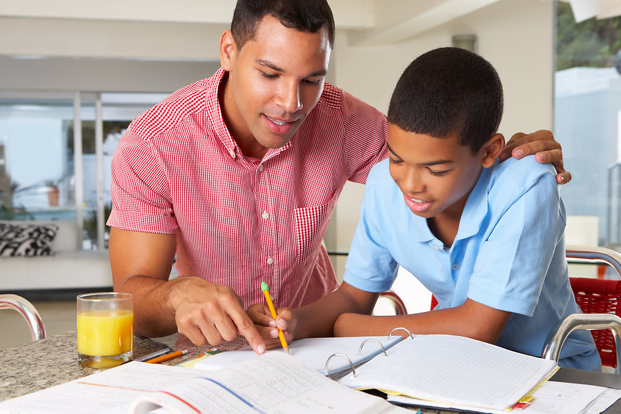 Father Helping Son With Homework In Kitc