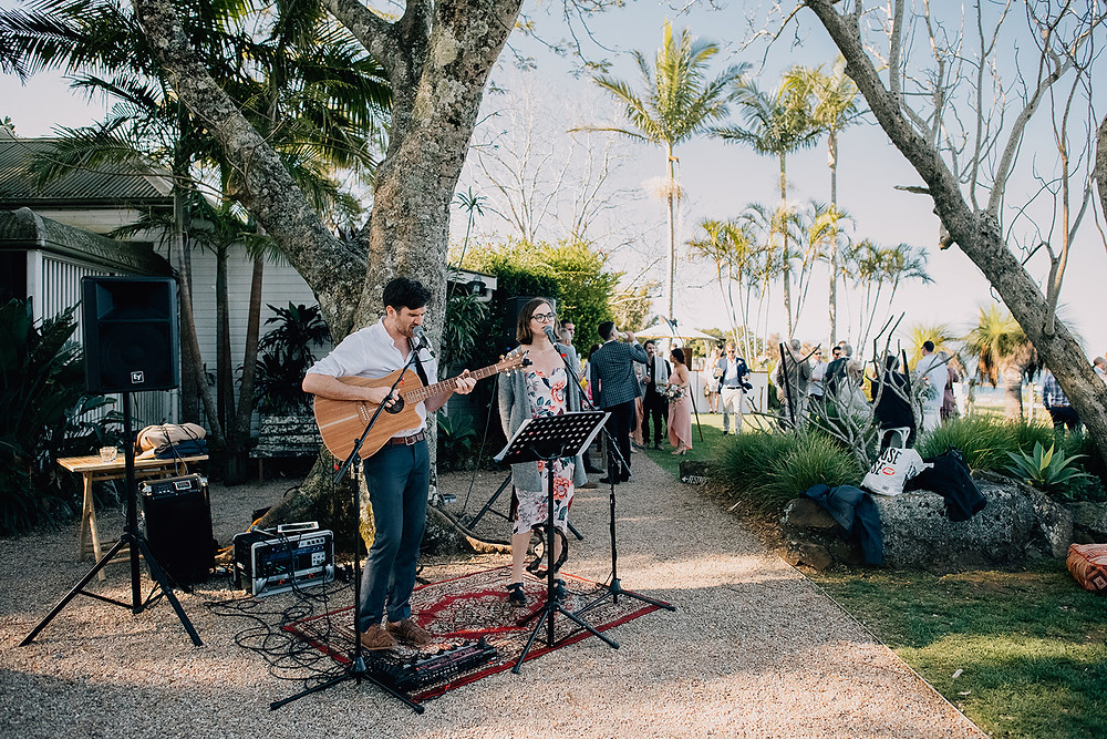"Wedding band, ""The Famo's Duo"" perform live music during canapes while guests mingle at wedding in Byron Bay,."