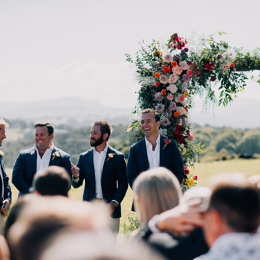 A Groom and his groomsmen wait at wedding alter for bride and bridesmaids to walk down the aisle.