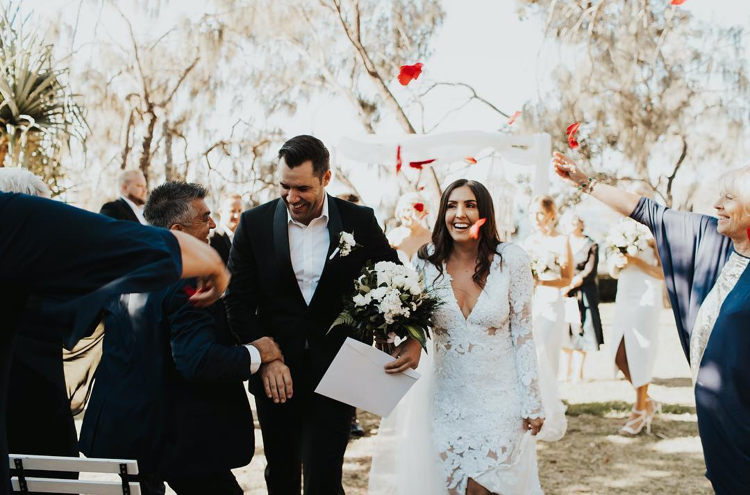 A newly wed couple walk back down the aisle together as the guests celebrate their marriage.