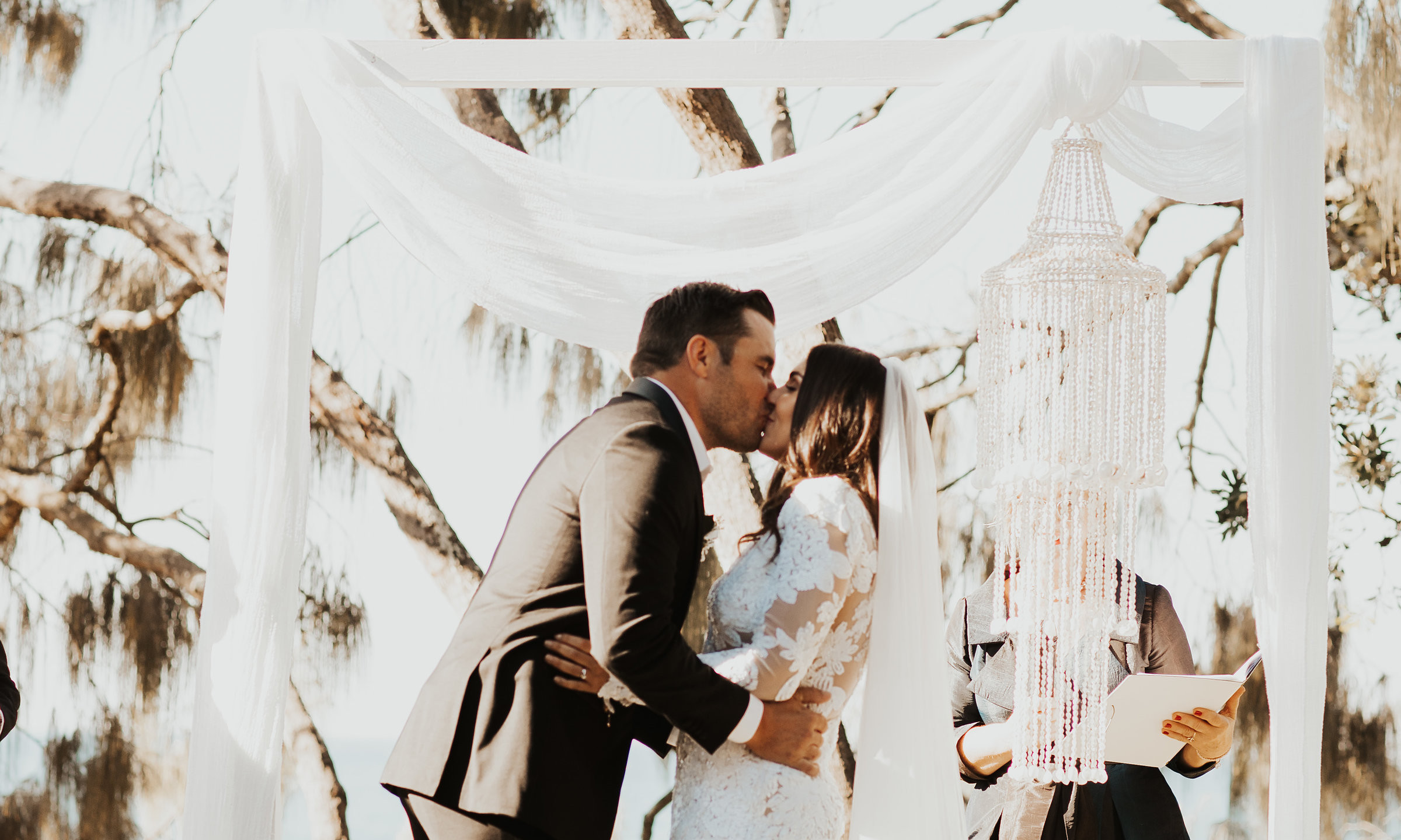 Bride and Groom kiss for the first time as husband and wife at a Noosa beach wedding ceremony