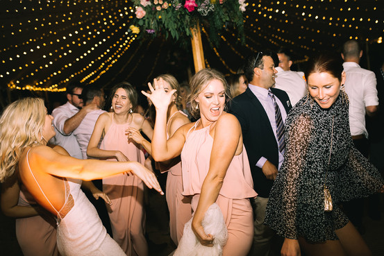 Bride and bridesmaids dance at wedding reception
