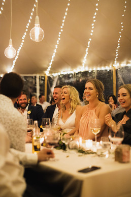 Newly Weds laugh during speeches at their wedding reception in Byron Bay