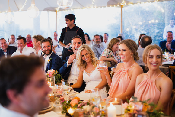 Bride and Groom laugh with groomsmen and bridesmaids at wedding reception dinner