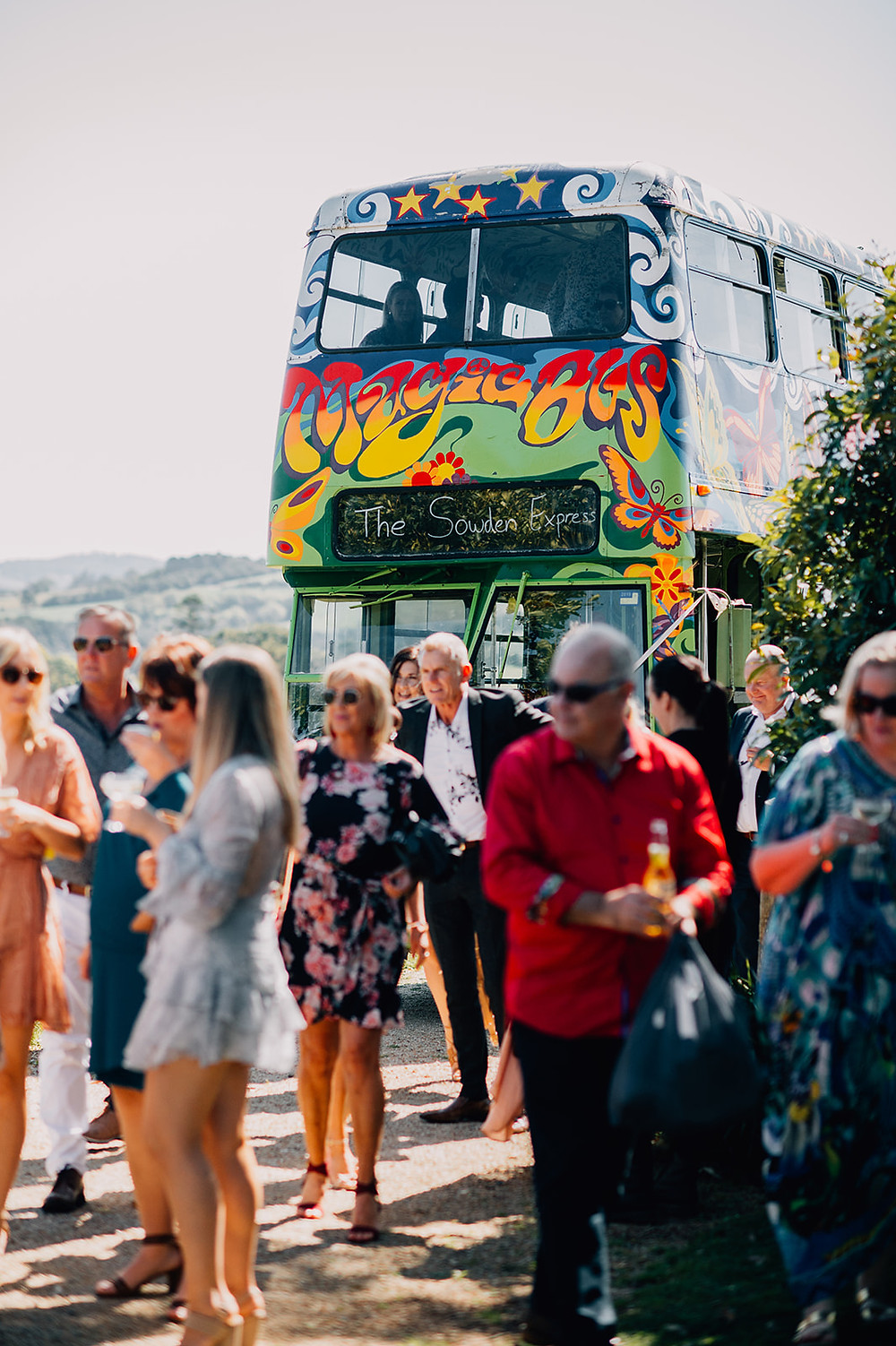 Guests arriving for the wedding ceremony on a double decker bus at Byron View Farm in Byron Bay, QLD