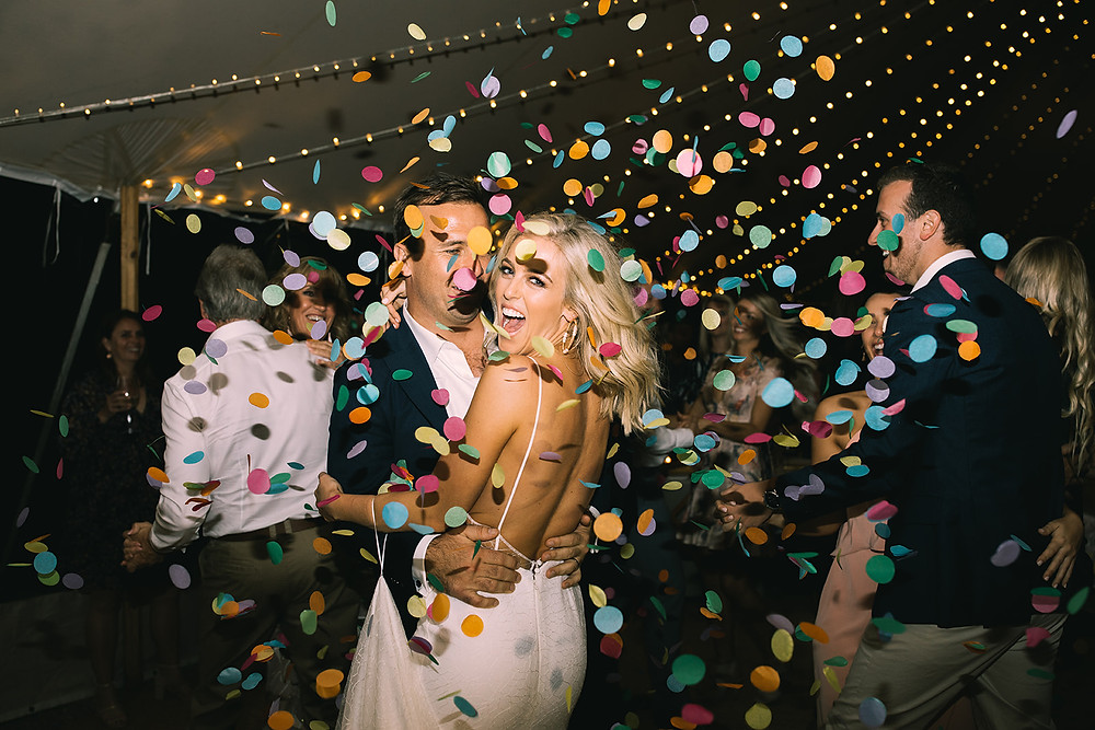 Bride and Groom dance as confetti is thrown over them at wedding reception