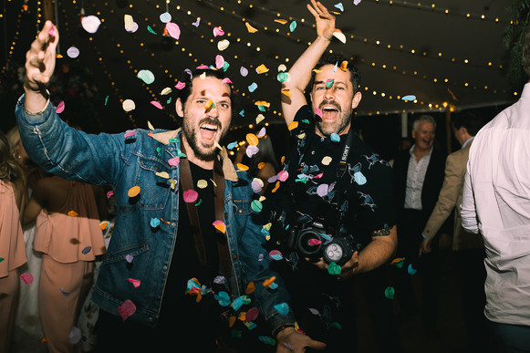 Two guests dancing at wedding reception while throwing confetti