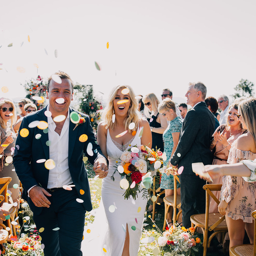 After just marrying, Groom and Bride walk back down the aisle as friends and family celebrate