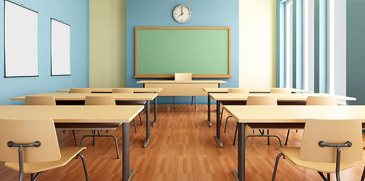 Bright empty classroom with beige desks and a chalkboard