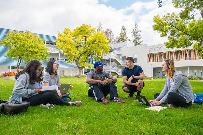 Students Sitting On Lawn Of SJCC
