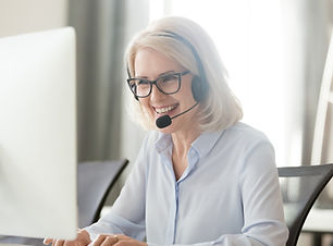 Happy old businesswoman in headset speak