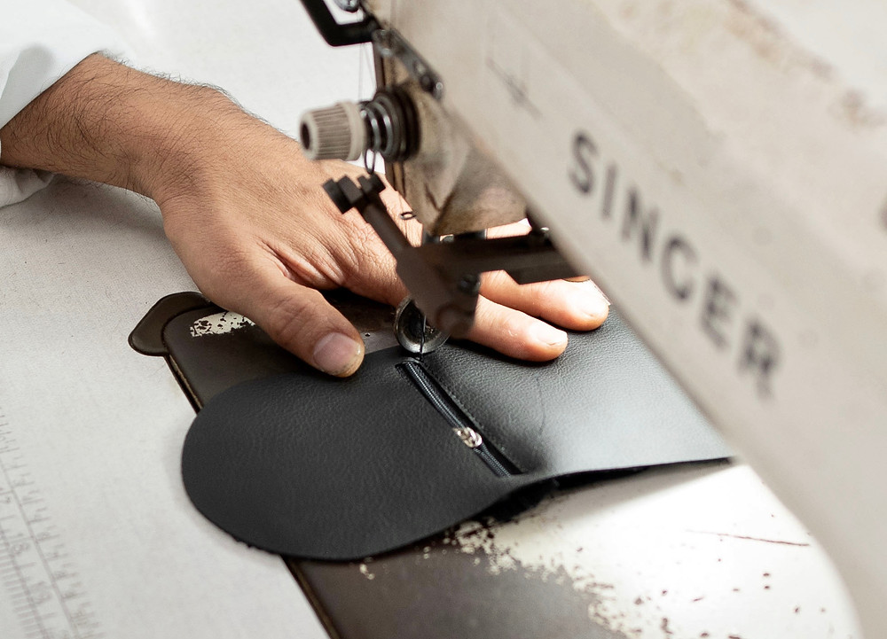 man sewing a vegan leather coin purse