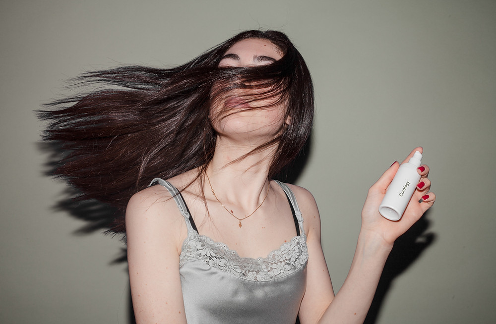 woman with blowing dark hair hold a spray bottle of dry shampoo