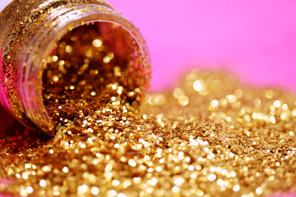 Pot of gold glitter spilling on a pink surface