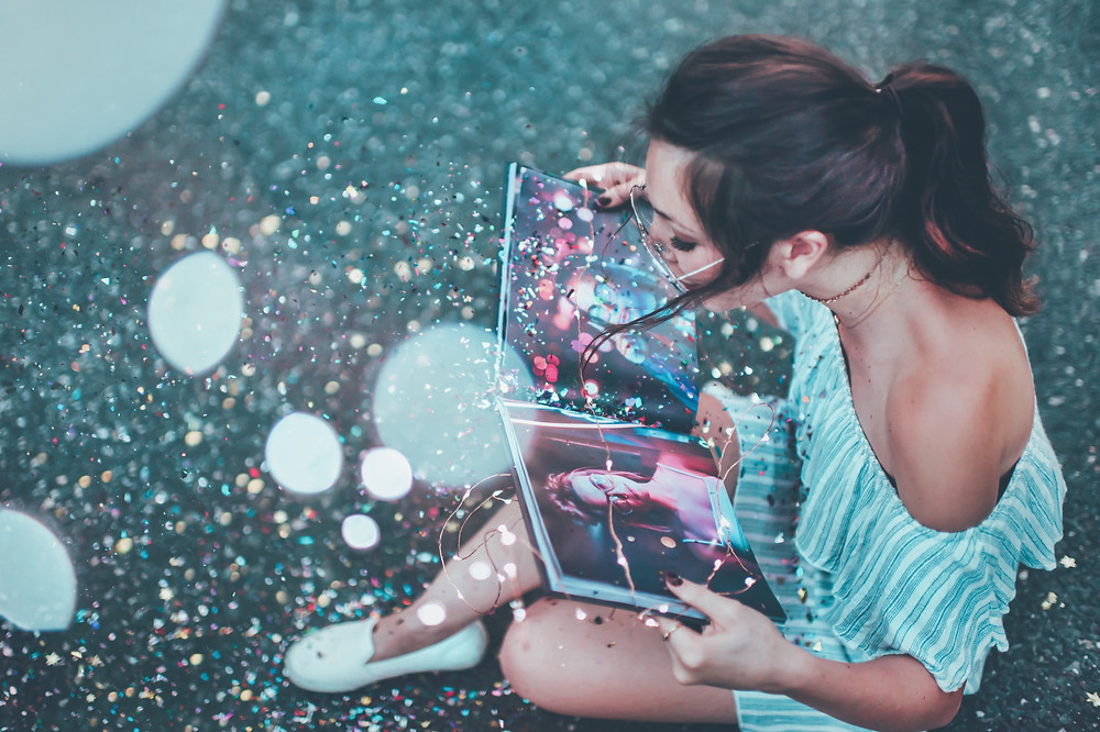 Woman blowing glitter out of a book into the air