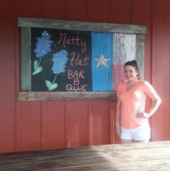 Girl Standing Next to Natty Flat Bar B Que Sign