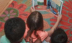 three kids reaing Riley te Brave Book on carpet
