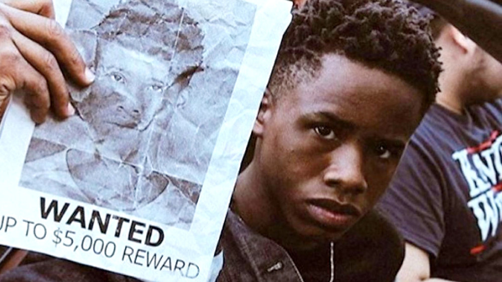 tay-k holding his own wanted sign