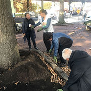 people working on a planter garden next to a sidewalk
