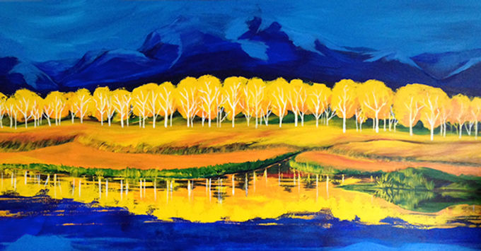 Yellow aspen trees in front of a blue mountain