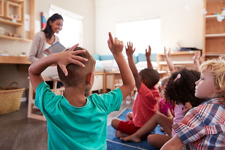 Pupils At Montessori School Raising Hand