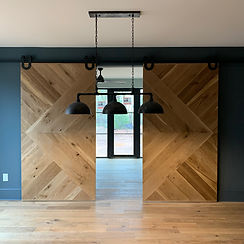 A pair of 62 Screws custom hardwood premium barn doors installed with modern black hardware in Milton, Georgia