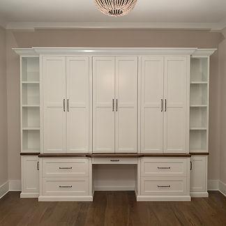 62 Screws custom luxury office built-in with oversized cabinets, hardwood modern desk, and floating shelves