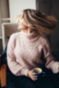 woman-sitting-on-chair-holding-blue-mug-