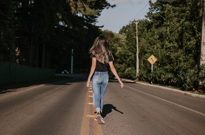 woman-in-blue-denim-pants-walking-on-roa