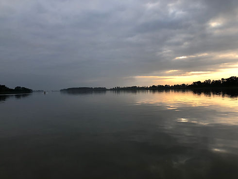 A rower is in the distance on a section of the river, the water is flat, with a sunrise appearing.