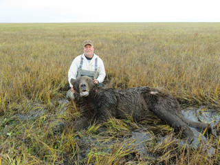 "John Jordan with his ancient old 9' 6"" boar he took in the ""swamp"". Judging by his teeth this old bear was in the 20 year old class."