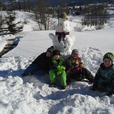 Kinder beim Schneemann bauen vorm Haus