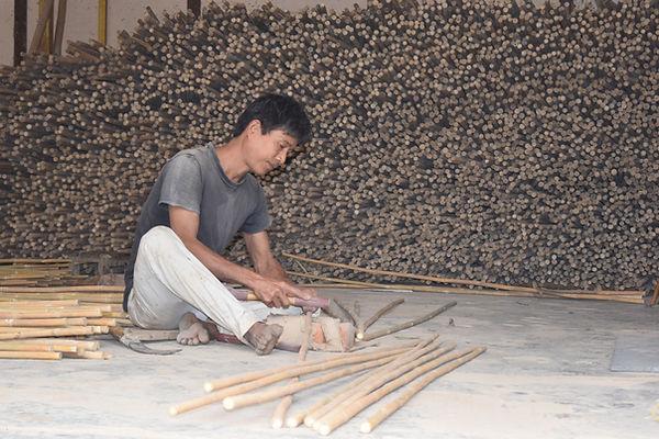 Craftsmen working with raw bamboo.